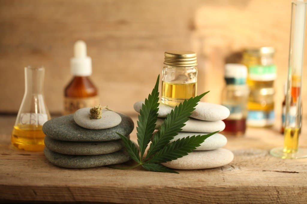 cannabis-leaf-resting-against-pile-of-stones-on-table-with-vials-and-bottles-of-cbd-and-other-essential-oils
