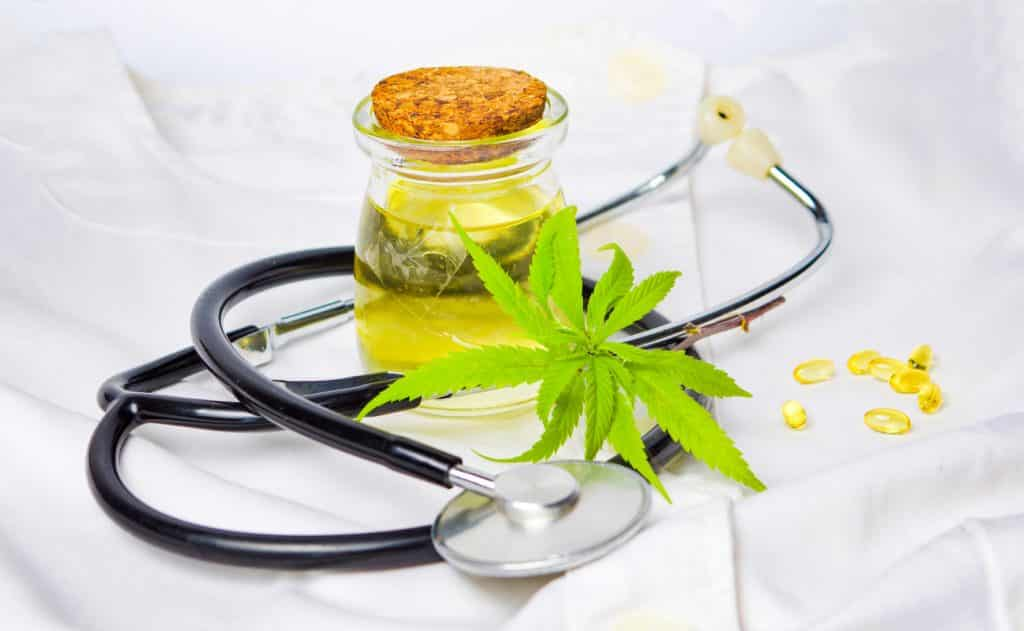hemp-leaf-cbd-oil-and-stethoscope-arranged-on-white-linens